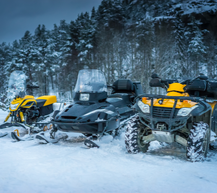 snowmobiles and atv outside in snow