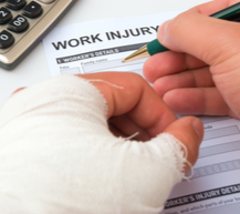 close-up of injured hand filling out workers comp paperwork